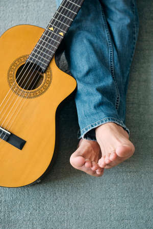 Barefoot Guitarist With Legs Outstretch Beside Guitar Imagens