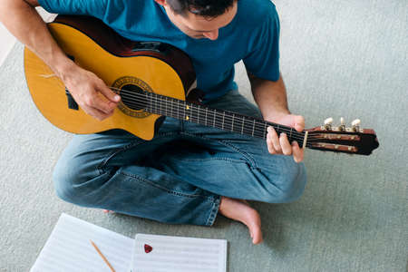 Mid Adult Man Reading Acoustic Guitar Sheet Music In Apartment Imagens