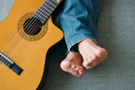 Barefoot Guitarist With Legs Outstretch Beside Guitar Фото со стока