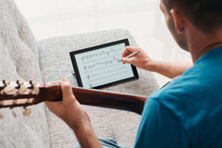 Man Composing Acoustic Guitar Sheet Music On Digital Tablet