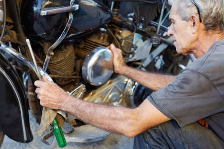 Senior Man Examining His Motorcycle And Fixing Engine