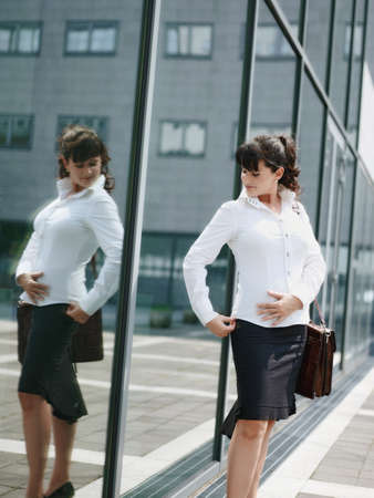 Mature Woman Losing Weight And Looking At Mirror In Office Window Фото со стока