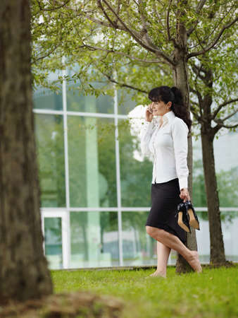 Mature Woman Standing On Grass Barefoot During Business Call
