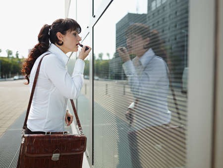 Businesswoman Applying Makeup Lipstick On Street Using Office Window