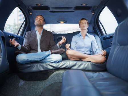 Businessman And Assistant Doing Yoga Sitting In Limousine Car