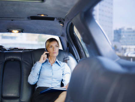 Businesswoman Talking On Mobile Phone Travelling In Limousine