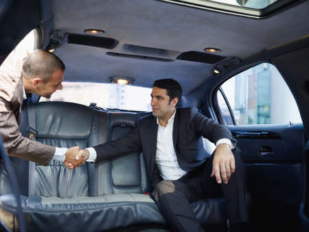 Businessmen Meeting In Limousine And Shaking Hands Фото со стока