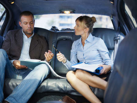 Businessman And Assistant Signing Contract Sitting In Limousine Car Фото со стока