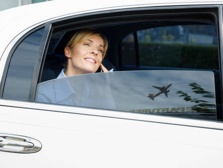 Businesswoman Arriving At Airport Talking On Phone In Limousine