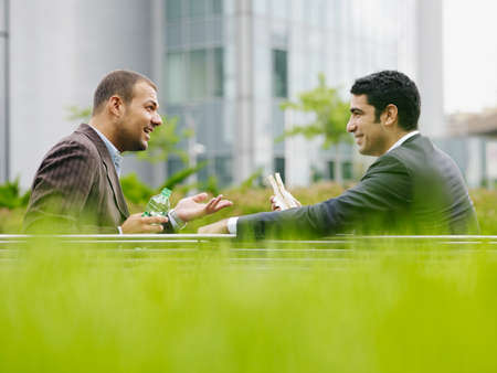 Two Business Men Enjoying Lunch Break Eating Sandwich Outdoors Фото со стока