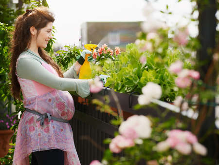 Young Pregnant Woman Spraying Water On Plants And Flowers Фото со стока
