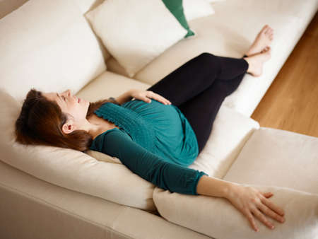 Young Pregnant Woman Lying On Couch And Touching Stomach Imagens