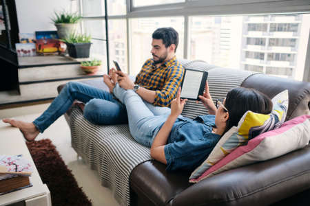 Young Couple Holding Ereader And Reading Ebook