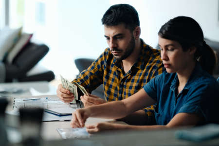Couple Doing Home Budget Counting Money To Pay Bills