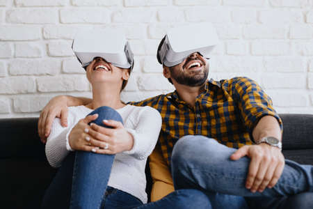 Young Couple Playing Virtual Reality With Headset On Sofa Фото со стока