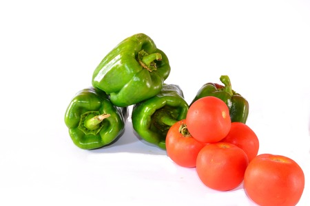 tomatoes and green bell peppers composition on white background photo