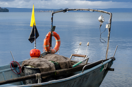 fishing nets hanging out to dry, boats and other fishing accessories on the shores of Lake Bolsena Stock Photo