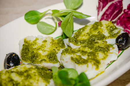 fillets of cod with herbs and olives sauce; typical Italian cuisine