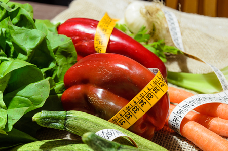 A measuring tape wrapped around the vegetables, healthy eating concept