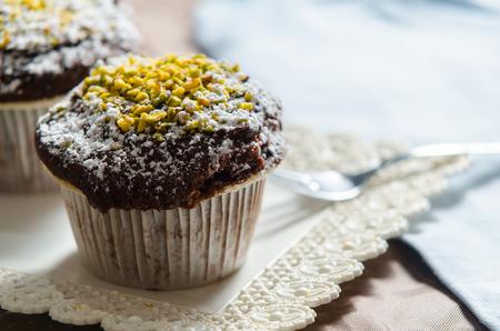 chocolate muffin with powdered sugar and pistachio grain Stock Photo