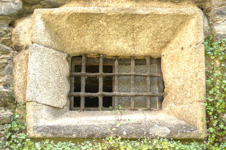 Small window with grating on the wall of the monastery 版權商用圖片