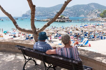 Two grandparents looking at a beach landscape in Camp de Mar, Majorca 스톡 콘텐츠