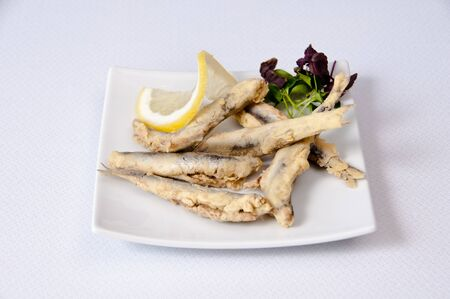 A plate of sardines on a white background