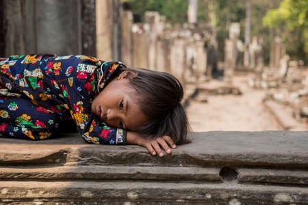 SIEM REAP, CAMBODIA - FEBRUARY 25  Unidentified traditional Khmer Cambodian child resting over temple ruins on February 25, 2013 in Siem Reap, Cambodia Stock Photo - 22409935