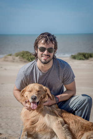 Young Male with Happy Dog Golden Retriever breed at the Beach. Argentina, South America. photo