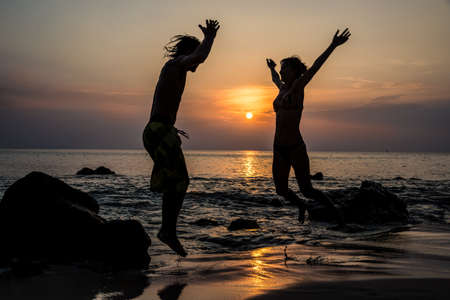 Happy Couple in Love Jumping, Fun. Tropical Island Sunset. Thailand. Asia adventure. photo