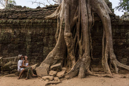Beautiful Couple looking at Giant Roots at Angkor Wat Cambodia. Traveling Asia Adventure. Incredible Journey. Stock Photo