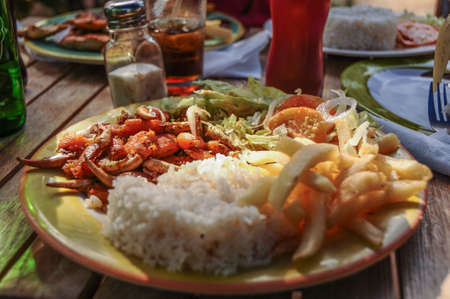 Enjoying typical meal of Crab Claws, legs, fried with french fries, rice and salad at San Andres island, Caribbean, Colombia. South America. Latin America.