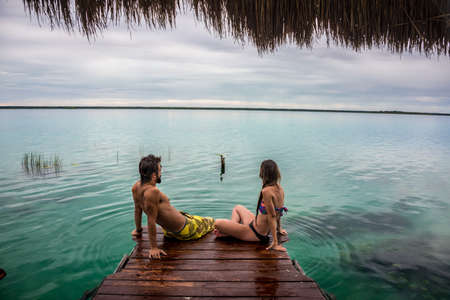 Riviera MAya의 Bacalar Lake, Quinatana Roo. 고민하는 dock에 앉아 몇입니다. 물 모션입니다. 스톡 콘텐츠