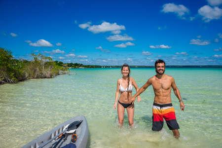 Bacalar kayak adventure, Lake at Riviera Maya, Quinatana Roo. Couple sitting on a dock contemplating. Water motion.