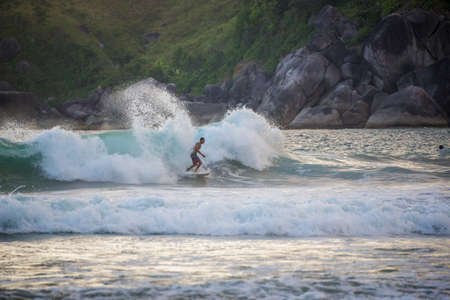 ILHABELA, BRAZIL-JANUARY 28: Young Male, Surfing and making tricks, enjoying beautiful beach of Ilhabela tropical Island at Sao Paulo, Brazil Editorial