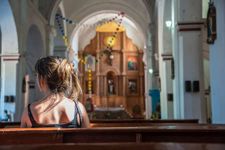 Religious scene young female praying at local church in Mexico.