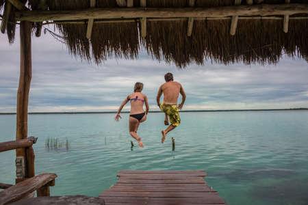 roo: Jumping at Bacalar Lake at Riviera Maya, Quinatana Roo. Couple sitting on a dock contemplating. Water motion.