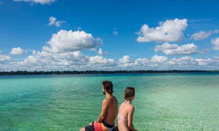 roo: Bacalar Lake at Riviera MAya, Quinatana Roo. Couple sitting on a dock contemplating. Water motion.