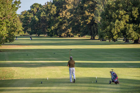 tee off: Golfer Swing and Tee Off at a beautiful golf course on Argentina, Buenos Aires. Healthy sport.