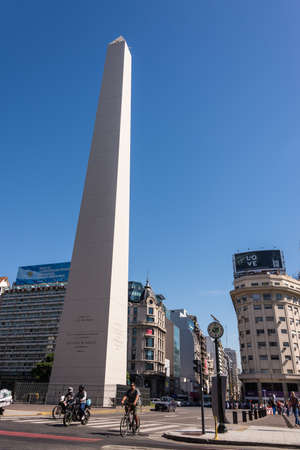 obelisco: Buenos Aires, Argentina - April 9, 2015: Unidentified business people driving down the street at iconic building  Obelisco on April 9, 2015 in Buenos Aires, Argentina