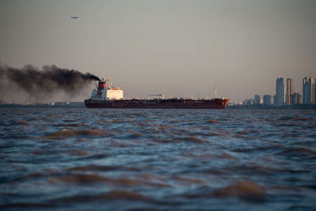 Cityscape South America. Cargo ship generating Pollution.