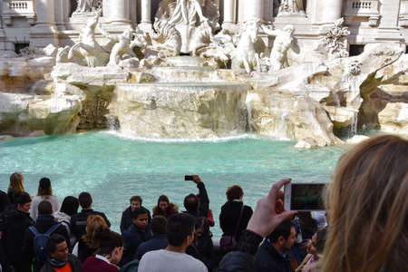Rome, Italy. February 11, 2017. People taking pictures at the Trevi Fountain on a sunny day (Fontana di Trevi)
