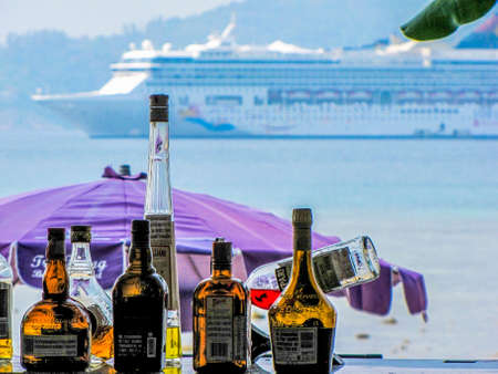 PHUKET, THAILAND - MARCH 12, 2013: Open air bar with a big cruise ship in the background. 報道画像
