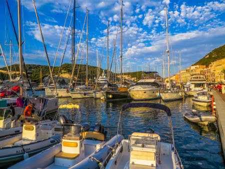 BONIFACIO, FRANCE - AUGUST 5, 2014: Boats and yachts on the port at sunset. Redakční