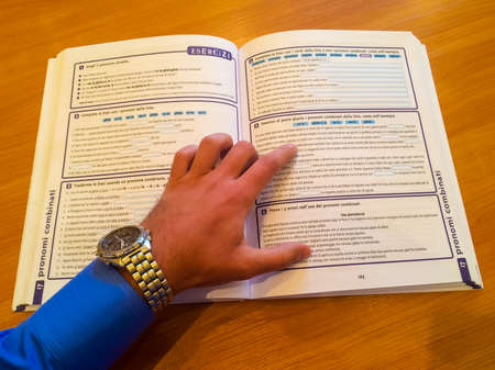 Studying Italian. Hand on opened book with exercises of Italian grammar Stock fotó