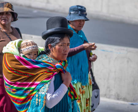 collective bargaining: Traditional Woman (Cholita) in Typical Clothes with baby on her back During 1st of May Labor Day Parade - La Paz, Bolivia