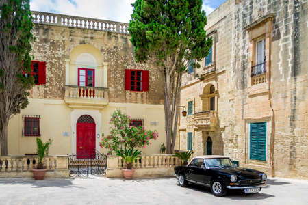 luxury house: Old stone house with colorful windows and black classic style convertible car - Mdina, Malta
