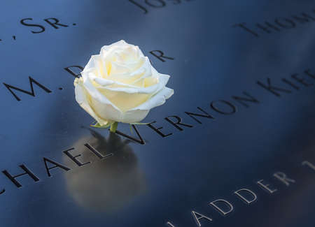 Birthday white rose left near name of the victim engraved on bronze parapet of 911 Memorial at Ground Zero World Trade Center - New York City, USA Editorial