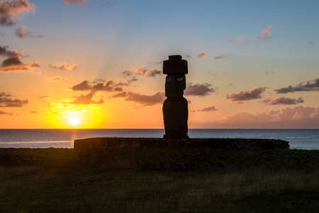 Ahu Tahai Moai Statue wearing topknot with eyes painted at sunset near Hanga Roa - Easter Island, Chile