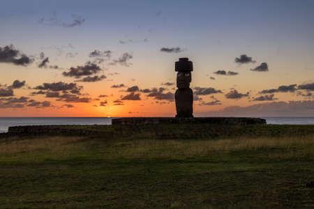 Estatua de Ahu Tahai Moai con un topknot con los ojos pintados al atardecer cerca de Hanga Roa - Isla de Pascua, Chile